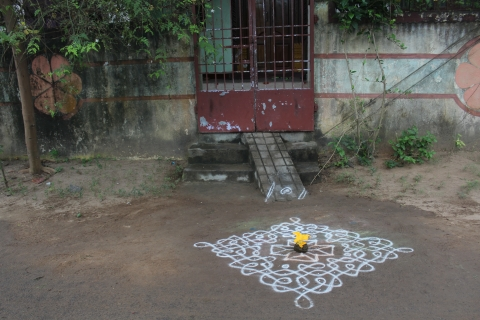 A traditional Sikku kolam made on the threshold of a house with cow-dung and pumpkin flower placed in the centre of the kolam.