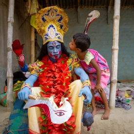 Basudeb Chowdhury Byadh, fully dressed in the character of goddess Kali, has a private moment with his 5-year-old daughter Bithi.