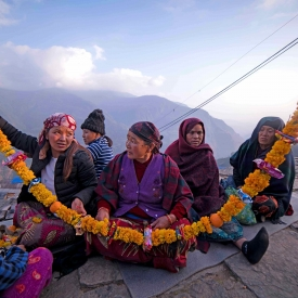 Women of the Gurung household weave together a garland for the departed soul; it is considered an offering that they might need in their journey to the afterlife. Hence, unlike regular floral garlands, these contain food items such as biscuits and snacks (Courtesy: Priyanka Chharia)