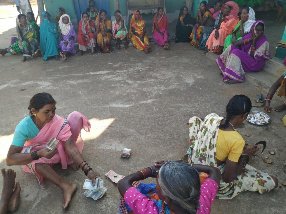 After selling the grains, the amount is being calculated so that every woman in the village will get their share of money.