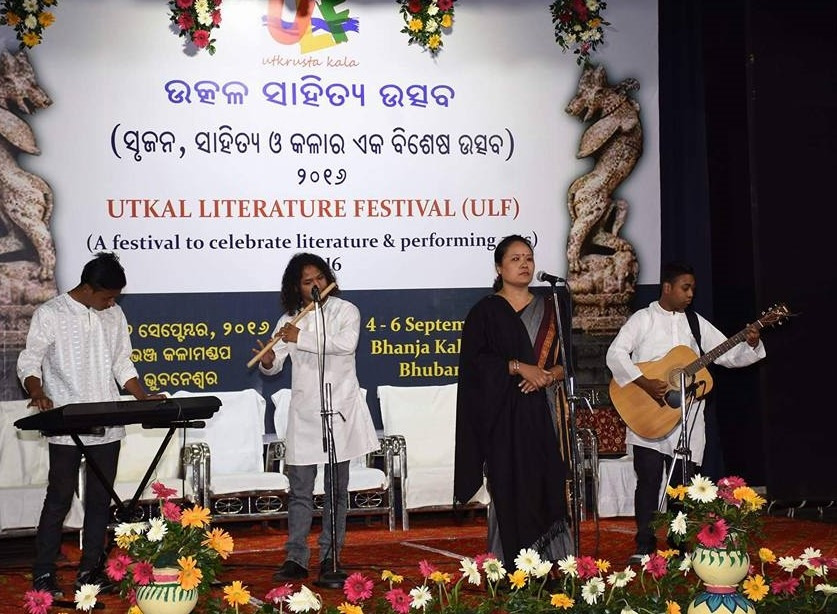 Fig. 2. Pavitra Lama performing avisangi kavita at Utkal Literature Festival, Bhanja Kala Mandap, Bhubaneswar, Orissa on September 4, 2016. Her performance is accompanied by live music played by the band Dhoka Aghi Mrityu Parkhandai. Lama's black shawl is part of the costume and marks her protest against child labour (Courtesy: Ganesh Sahoo)