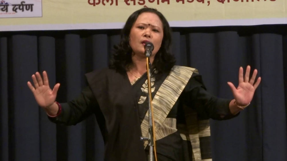 Fig. 3.Pavitra Lama performing her poem, 'Chourastaa' at the Gorkha Dukha Nivarak Sammelan Hall, Darjeeling, West Bengal on June 11, 2017. Lama's black shawl here is an indicator of the silent protest against the imposition of the Bengali language in secondary schools in the Darjeeling Hills where maximum students are Nepali speakers (Courtesy: Rajesh Wokamchha Rai)
