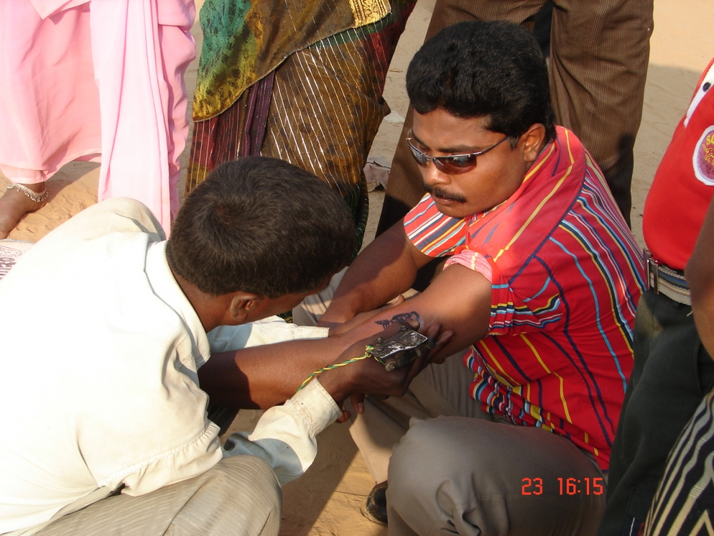 A man getting godna on his arm