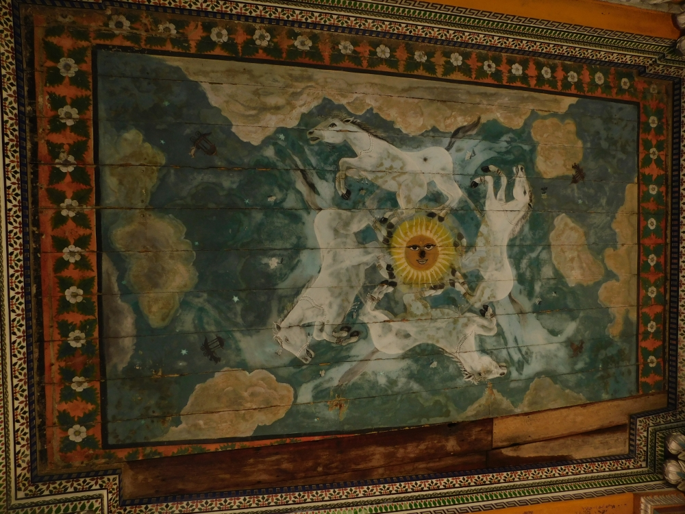 Fig. 6: A smiling sun surrounded by four running white horses among stars, falling flowers, and clouds. Four unoccupied horse-drawn chariots on the four corners of the composition can be detected. Their small size may suggest distance. This painting may have been done by Muskare as there is no mention of any other painter involved with the temple (Photo courtesy: Sritama Halder)