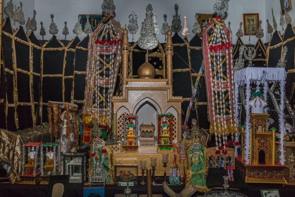 Fig. 8: A replicated rauza of Imam Hussain (a.s.) made of wood placed in an azakhana. Taziya and zarih of different sizes can be seen along with alam in the background