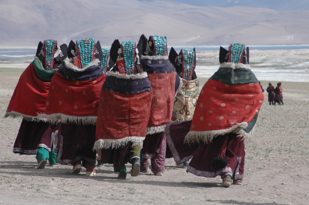A group of women in Rupshu, Changthang, are all dressed up to attend a Horse Race near the Tso Khar lake. They are all wearing perags with four or five lines of turquoise. Also, visible, on either side of the head, are the silver chains (thenthak) holding the perag and earflaps in place. Two of the women, on the left, have the additional coral strip stitched on to the side of their perags. This is indicative of greater prosperity. A large yarn tassel (geblin) can be seen below the cape of the woman on the right. (Photographer: Monisha Ahmed, 2006)