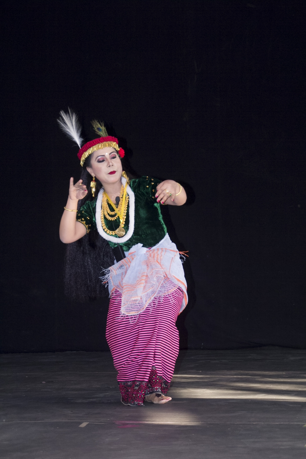 Fig. 1: A dancer performs the Khamba Thoibi dance, a thougal jagoi (dance in service of gods) performed during the Lai Haraoba (pleasing of the gods) festival, Manipur. Thoibi's ensemble includes a phanek mayek naibi (striped phanek with embroidered borders), resom phurit (blouse made of dark green glossy fabric, embellished with sequins), white khwangyet (waistcloth) knotted at the centre, kajenglei (a red headdress with golden fringes and a peacock feather tucked on top) (Courtesy: Jawaharlal Nehru Manipur Dance Academy (JNMDA), Imphal).