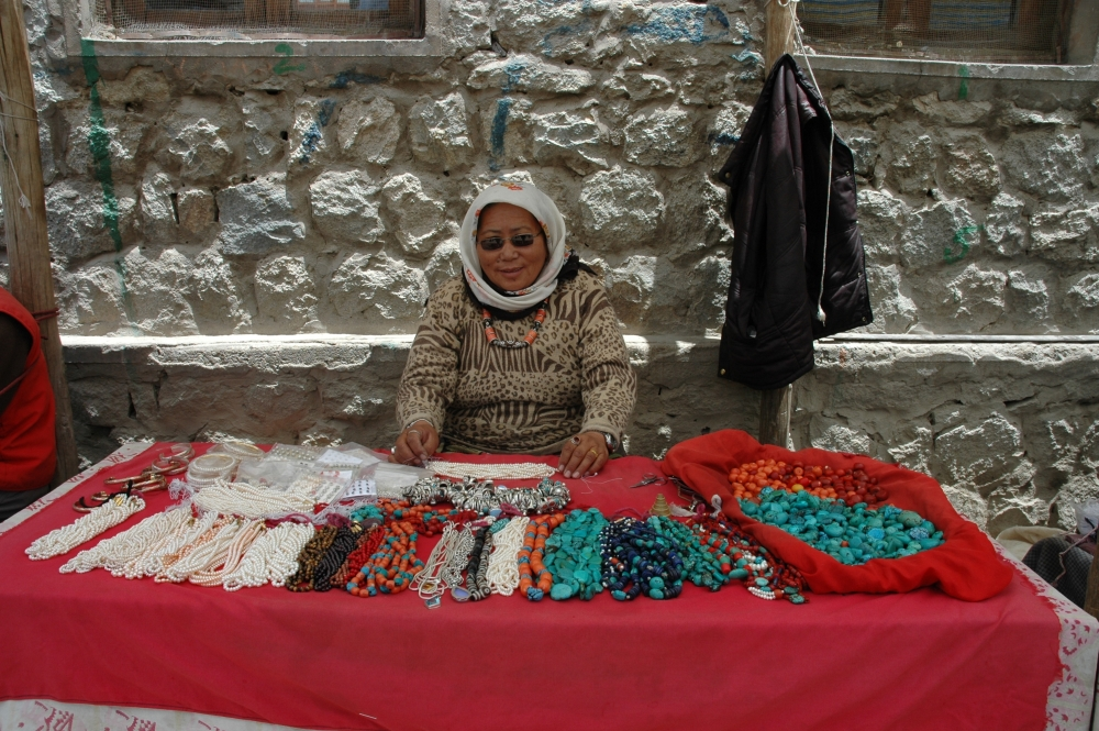 Fig. 12.A Tibetan trader sets up shop along the pathway in Leh market, selling coral, pearls, turquoise, and an assortment of silver pieces. Some of the stones are strung, while others are not. These are mainly flat turquoise pieces that Ladakhi women buy for their perags. She is wearing a necklace with one large central dzi (etched agate) and four smaller ones, strung together with coral stones. (Photographer: Monisha Ahmed, 2005)