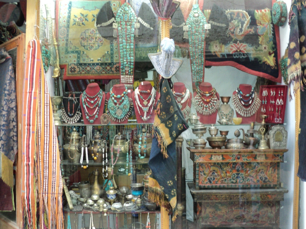 Fig. 13.The window of an antique shop in Leh shows old peraks and an assortment of old and new necklaces and earrings for sale. On the bottom shelf, centre, is a pair of conch-shell bracelets. Apart from an assortment of teapots, religious objects, textiles and low wooden tables. (Photographer: Zahera Bano,2010. Courtesy: LAMO Visual Archive)