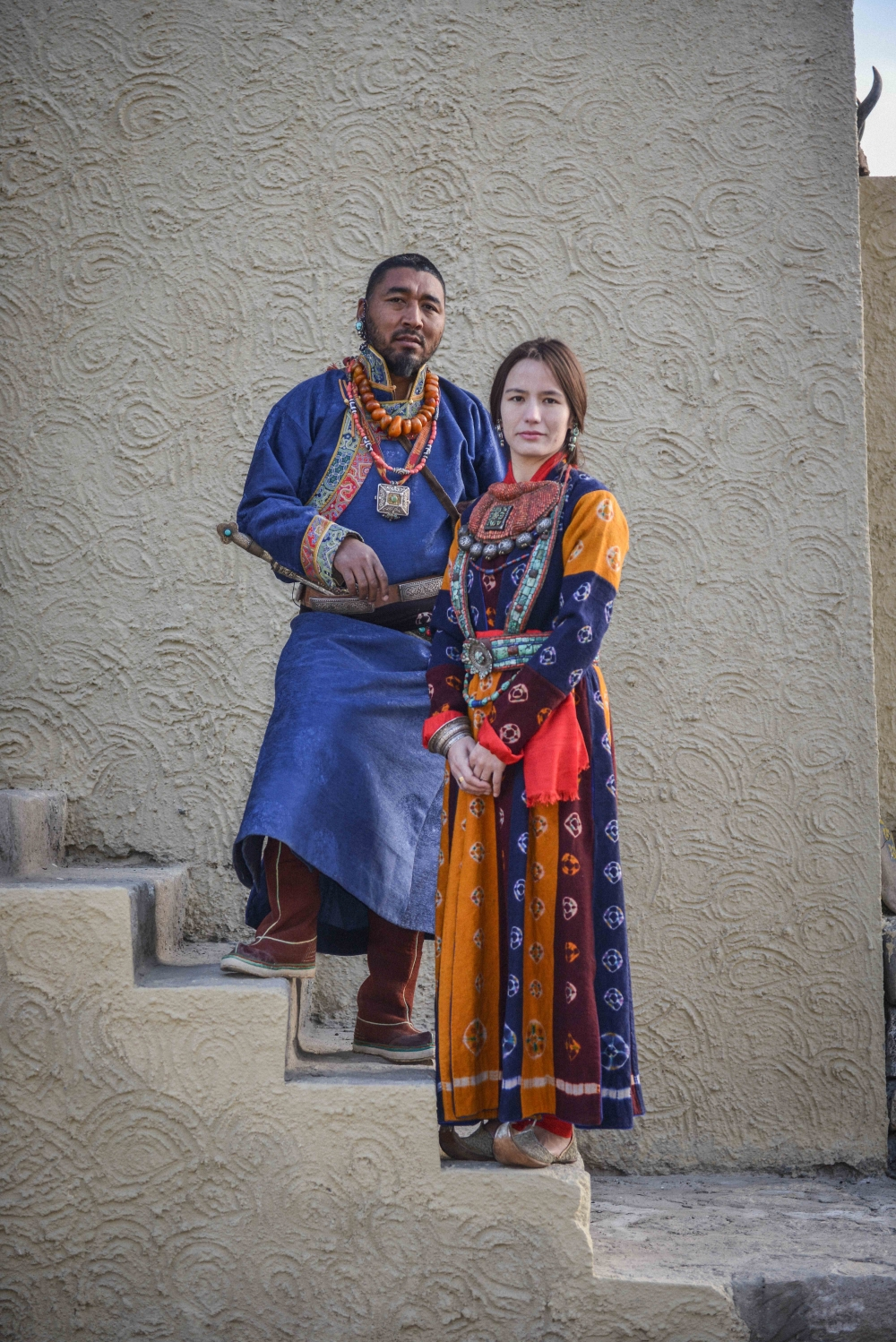 A campaign shoot for the label 'Jigmat Couture' shows two models dressed in contemporary yet traditional Ladakhi dress and jewellery. The man is wearing three necklaces – one amber, one with five dzi strung with coral stones, and a silver filigree worked amulet (gau) hung from a silk fabric. He wears a silver and turquoise earring, supported by a loop around his ear. A leather belt decorated with silver worked pieces placed at intervals; the dagger inserted into it has a silver hilt with a single turquoise stone. The woman is wearing a large gorget, a stiff collar piece (skebug), made from a piece of padded red cloth onto which a central silver and gold-plated amulet is stitched, surrounded by lines of coral, with a fringe of seven silver amulets. She is wearing turquoise and silver earrings. Around her waist is a turquoise and coral belt. On her right hand she is wearing a silver bracelet embossed with Buddhist and geometric patterns.   (Photographer: Bablu and Sonny Singh, 2017; Courtesy: Jigmat Couture.)