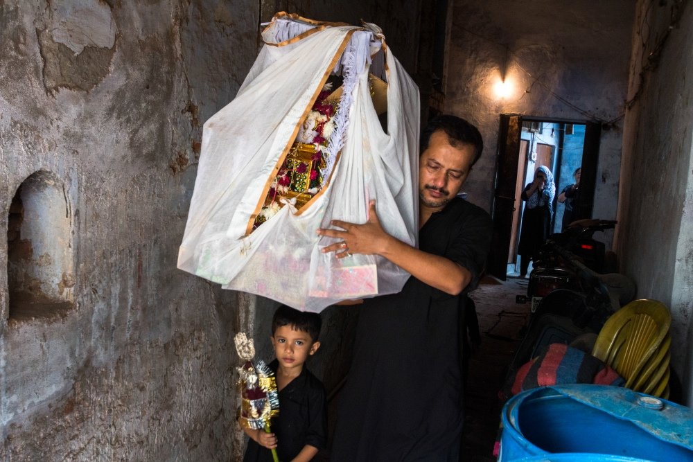Fig. 7: A man with a child holding an alam (flag) takes a taziya for burial. The end journey of a taziya is usually on the tenth day of Muharram when it is draped in cloth with flowers that adorn it in an azakhana