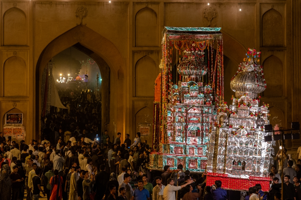 Fig. 9: People at Shahi Juloos to witness the Shahi Zarih of Hussainabad Allied Trust at Rumi Gate in Lucknow. The zarih layered with wax (left) is accompanied by a smaller bamboo taziya layered with arbak