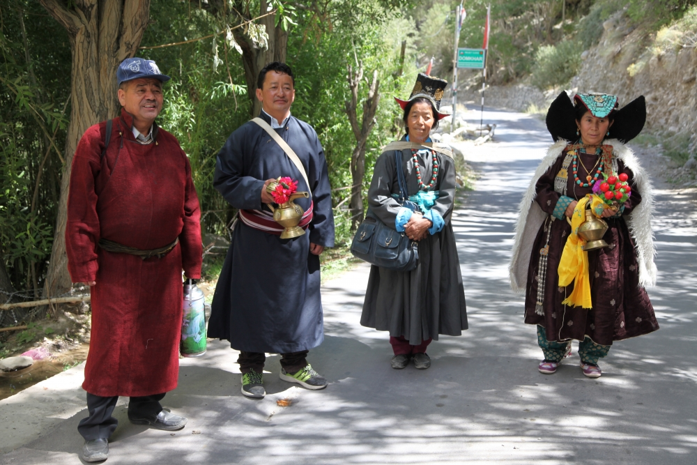 A group of people, dressed in their best, on their way to attend a ceremony at the monastery in Dumkhar village. The two men are dressed in the male robe (gos), while the one on the left wears one made from locally woven woollen fabric (snambu), the one on the right wears one stitched from imported polyester. The women are dressed in sulma, the one on the left wears one made from polyester with a machine-embroidered velvet hat (tibi).  The woman on the right wears a silk-brocade robe with a turquoise-studded headdress (perag). Over her shoulders she wears a cape (sbog) made from silk-brocade, lined with imitation goatskin. (Photographer: Tsering Wangchuk Fargo, 2015)