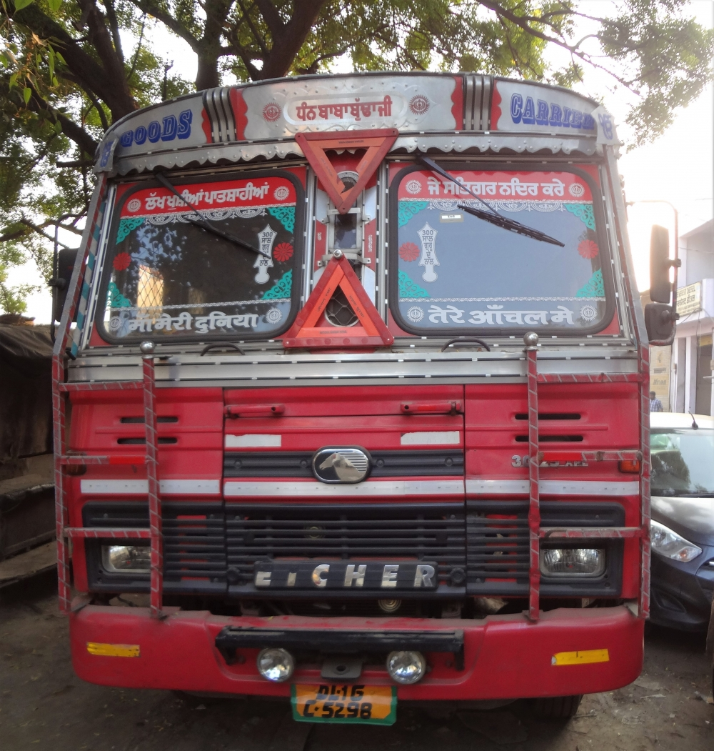 Fig. 2: The script of truck literature depends on the linguistic identity of the truck driver or the owner. One of the most common themes of truck literature in North India is the invocation of gods and one's parents. Also striking in this photo is that the truck is much less decorated as compared to the trucks from other states. This has to do with strict guidelines on truck registration in Delhi, which leave little space for personal indulgence.