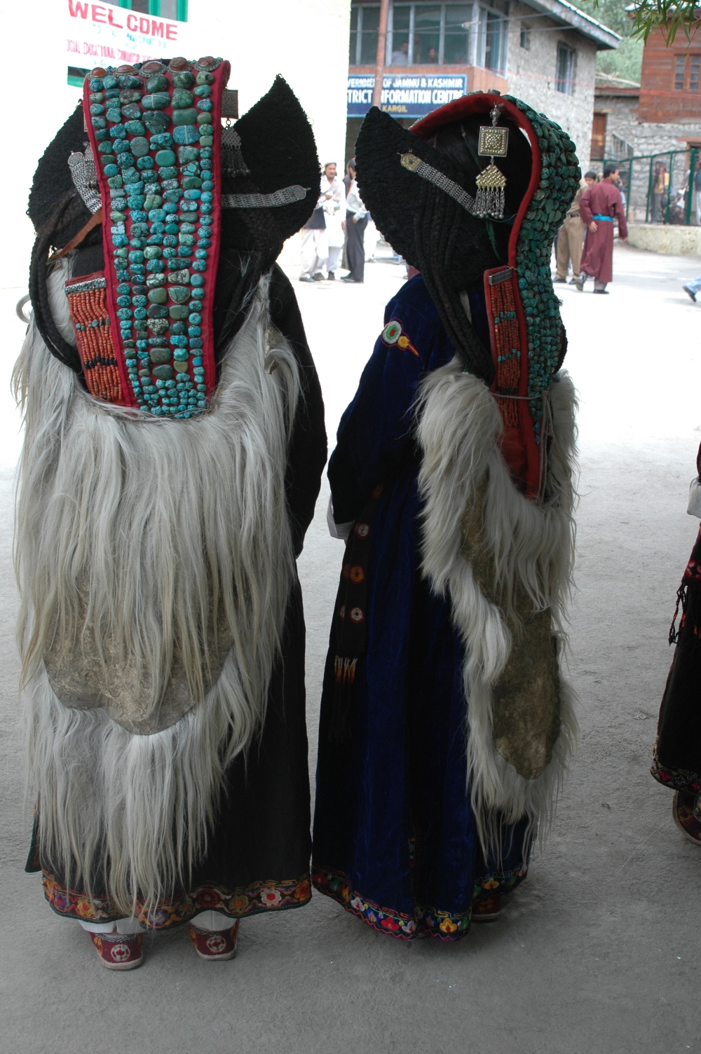 At a celebration in Kargil, two women wearing their perags (turquoise-studded headdress) along with capes made from goatskin (slog-pa) over their robes. The edges of their robes have a piping of hand-embroidered floral motifs, common in the region (Photographer: Monisha Ahmed, 2005)