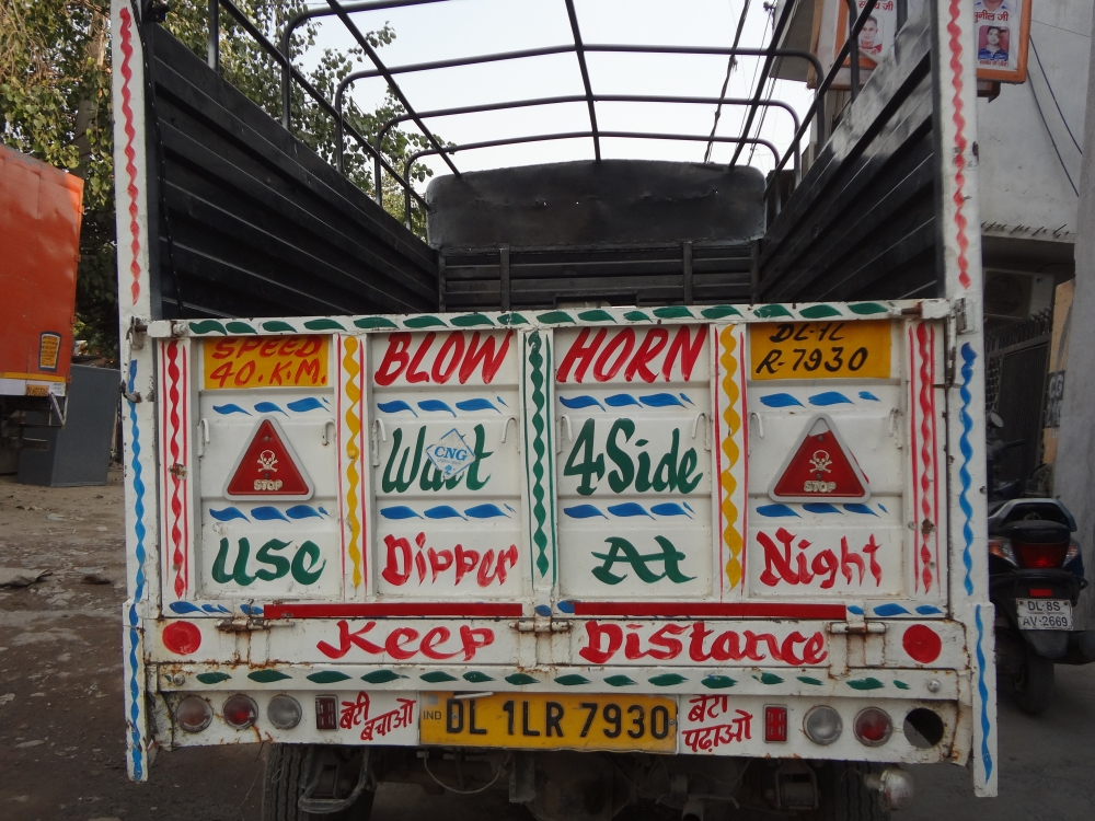 Fig. 3: Truck literature has diversified into various other forms of transport. This pickup truck parked at Delhi's Sanjay Gandhi Transport Nagar carries writings three different phrases that appear commonly on trucks, 'Use dipper at night', 'Keep distance', and 'Wait for side'.
