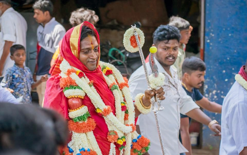 Fig. 3. The Karaga priest returns from Jalakanteshwara temple in Gavipuram after finishing  the Gange puje on day five of the festival. Every morning throughout the festival, the priest travels to different sites across the city to perform rituals and then return to Dharmaraya temple by evening (Photo courtesy: Prashanth B. Vepuri, Revival Heritage Hub)