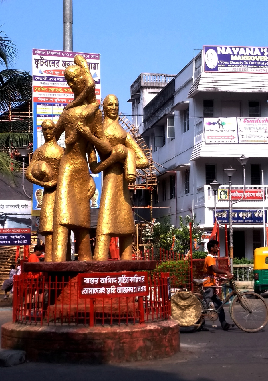 Fig. 4: Netajinagar: The refugee statue and the colony committee office on the right-hand corner. Behind the statue is a glimpse of the pandal of the colony committee puja being made. Courtesy: Priyankar Dey