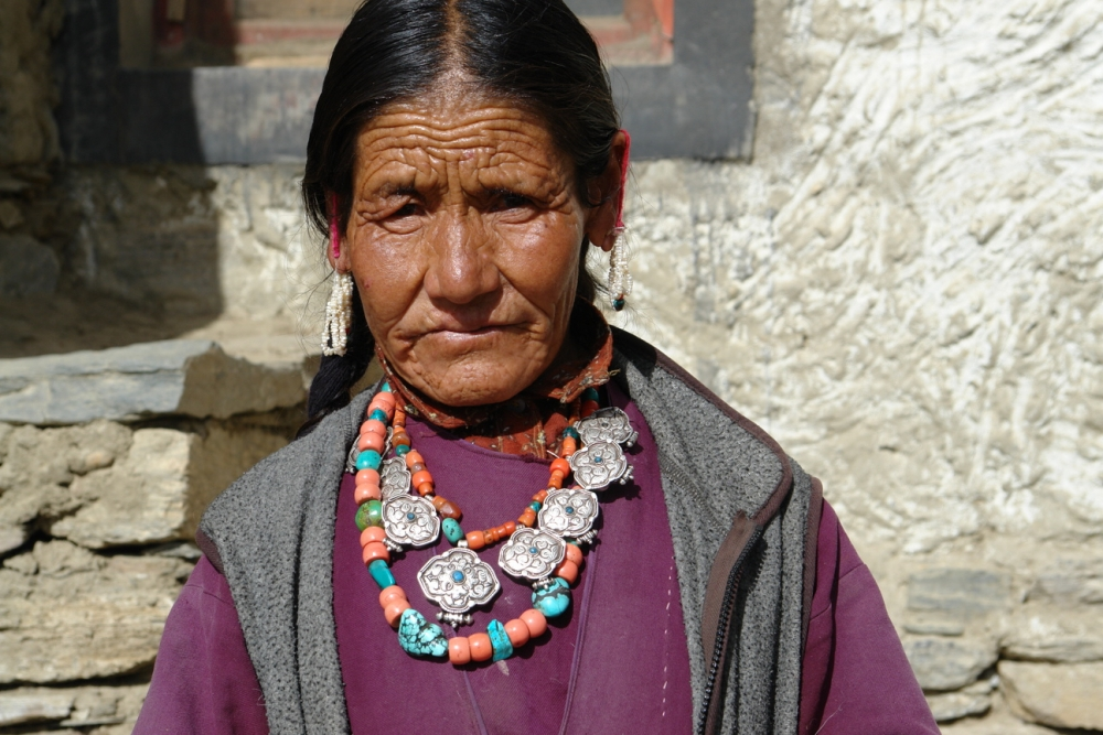 The woman shown here is wearing two necklaces—one consists of a series of eight silver amulets, strung together on a strand of coral beads, with a central turquoise stone. The second necklace consists of large coral and turquoise stones. In her ears she is wearing several strands of pearls with a small turquoise and coral stone on either side, at the end. A loop of red yarn around her ears takes the weight off the hole in her ear. (Photographer: Monisha Ahmed, 2007)