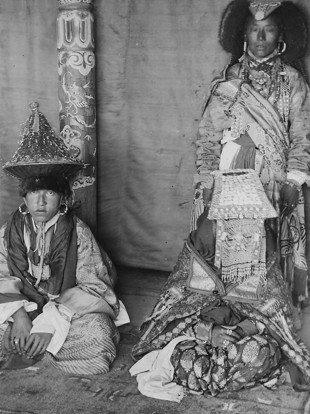 At the royal wedding in Stok, the crown prince Jigmet Dadul Namgyal and his bride queen Nyilza Wangmo are dressed in all their finery. The bride is dressed in an elaborate perag with a veil of basra pearls covering her face. Her perag is larger in the front than most typical ones worn by women in central Ladakh. She is also wearing a number of silver and gold rings. The crown prince is wearing a hat (serthop) covered with golden coloured threads, he wears large hooped earrings and around his neck hangs an amulet box (gau). (Photographer: Sebastian Schmitt, 1907–13; Courtesy: Gisela Müller)