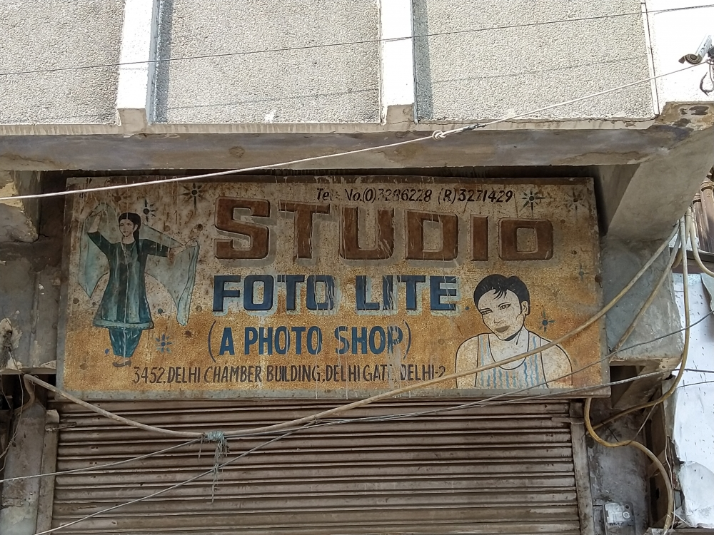 Fig. 6. A signboard of a photography studio in Delhi Gate, which is an example of signage with illustrations. With an image of a man in a vest and a woman flaunting her chunri, Studio Foto Lite's delightful signboard has the title shape of a megaphone that recalls the typographic designs similar to the poster of the 1974 film Bidaai.
