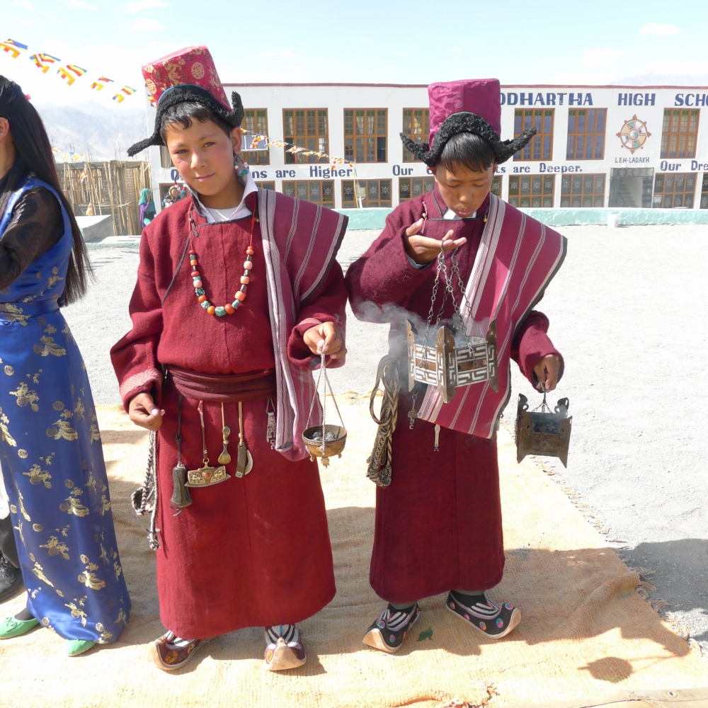 At a school ceremony, these young boys attend dressed in male Ladakhi attire. They are wearing woollen robes and silk brocade hats. From the belt of the boy on the left hangs, from left to right: a sling shot, leather needle case, metal ornamented flint purse, brass spoon, wood and metal knife and brass key. Around his neck is a necklace with coral and turquoise stones. In his ears are a loop of turquoise, imitation coral and pearl beads. (Photographer: Monisha Ahmed, 2015)