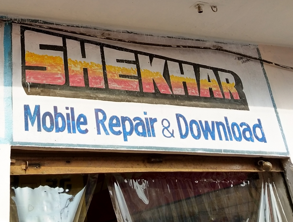Fig. 8. The signboard for Shekhar, a mobile repair shop in Chandni Chowk, has the eye-catching features of cinema title design. The red, white, and yellow used to fill the letters resemble the effect of crayons and the thick black shading encases the lettering and pronounces its shape.