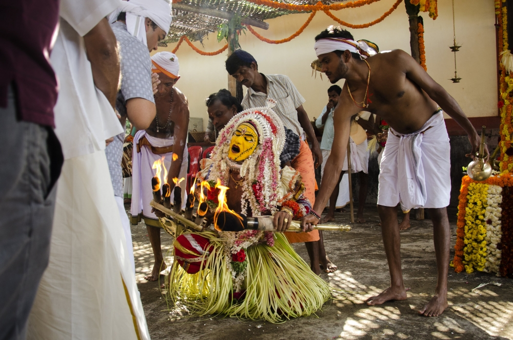 Fig. 1: Bhootakola at Orvadi Guttu, Hiriyadka. The paatri is seen paying his respects to the owner of the Orvadi Guttu. Every bhootakola event begins with this tradition where the paatri first pays respects to the guttu owner before the proceedings