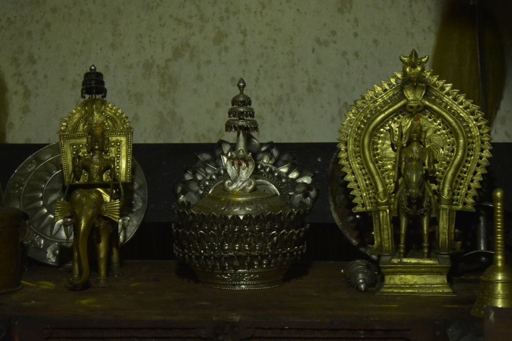 Fig 2:A shield, a silver crown, a bell, and statues of the guardian spirits, Baiderlu (riding an elephant) and Kodamanithaya at the daivakone of Kallya Guttu. The room also houses other materials not kept in a decorative manner, such as a bronze cradle and swords.