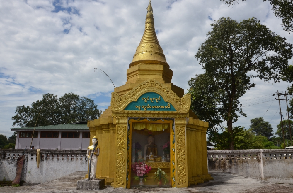 Fig. 3:Vasundhara, with her flowing hair, is placed in front of the Buddha's shrine in Chongkham Buddha Vihar, Chongkham, Arunachal Pradesh. Vasundhara, the earth goddess, is sometimes placed as a guardian deity in front of the Buddha's shrine. In the legend associated to her, on the Buddha's call she caused a flood by wringing her hair to drown Mara's army
