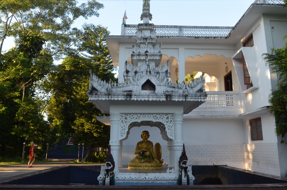 Fig. 5:A large sculpture of Upagupta, surrounded by an artificial pond in Pariyatti Sasana Buddha Vihar, Namsai, Arunachal Pradesh. According to legends associated with him, he is still alive under water, waiting for the future Buddha. Large sculptures of Upagupta are placed inside shrines which are decorated with ornamental motifs and mythical creatures