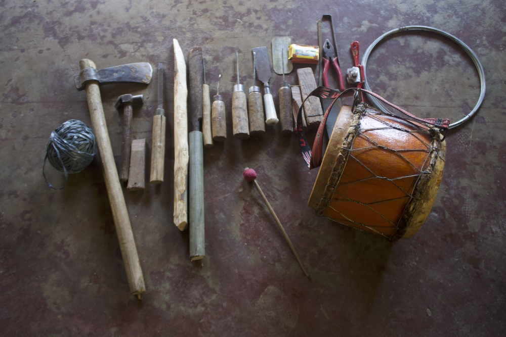Fig. 5:Nkhuangh, viewed from the top, with the tools required for its construction. These iron tools are required for carving and hollowing out the dense wood and giving it a drum shape (Courtesy: R. Husuang)