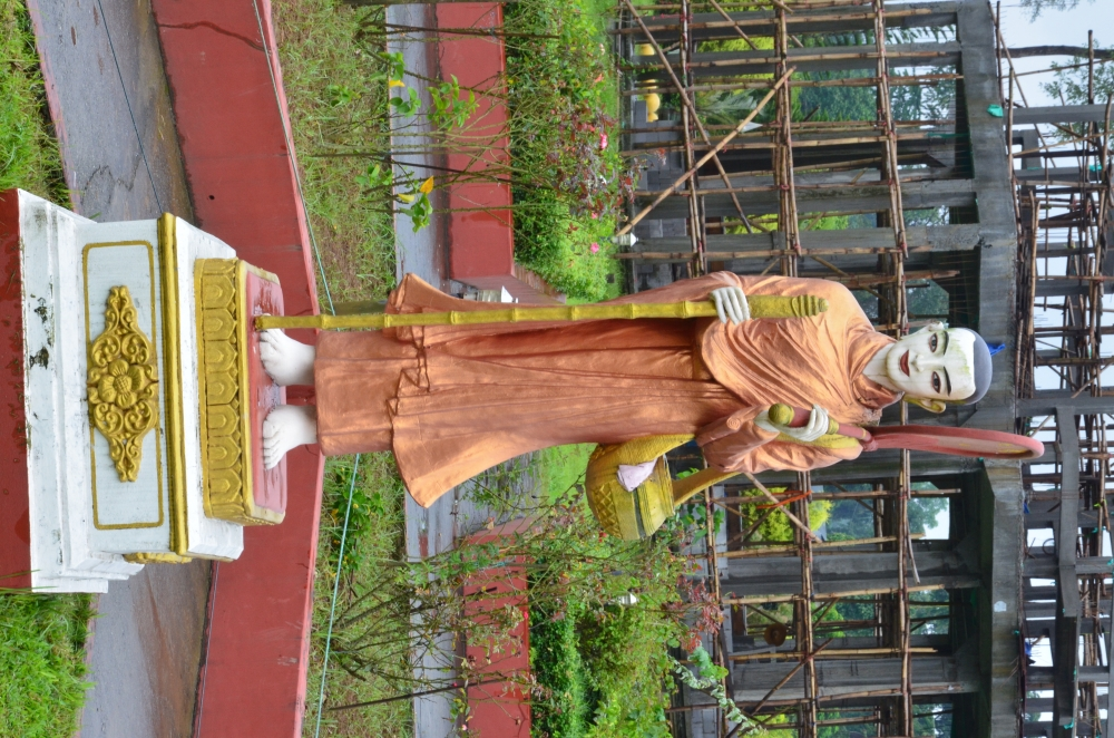 Fig.6:A large sculpture of Sivali in Kongmu Kham (golden pagoda monastery), Tengapani, Arunachal Pradesh. A disciple of the Buddha, Sivali is the patron saint of travel and harbinger of fortune. In his images, he is represented as a travelling monk. He holds a walking staff, an alms bowl, and a shade for protection from the sun