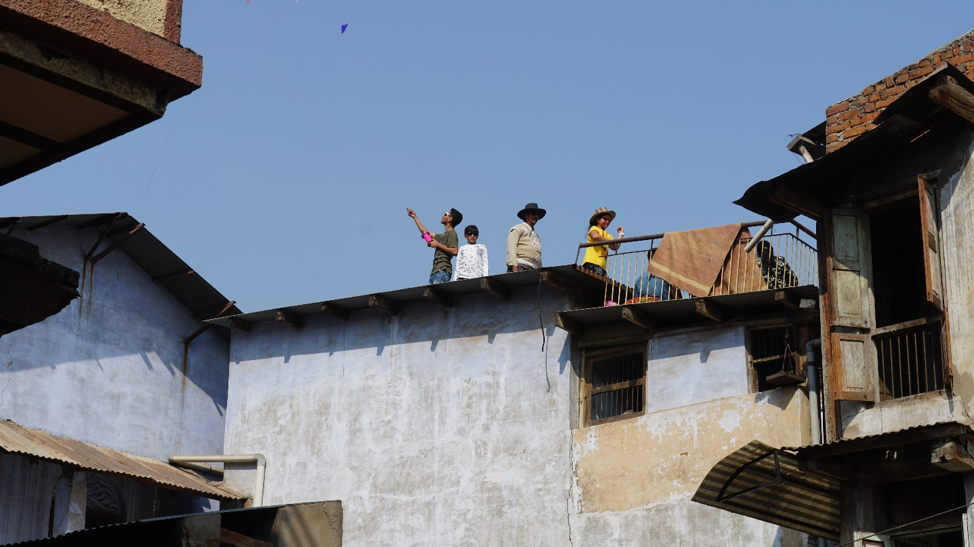 Fig. 7: A family flying kites on a sloping rooftop in Khadia, Ahmedabad. (Courtesy: Ashna Patel)