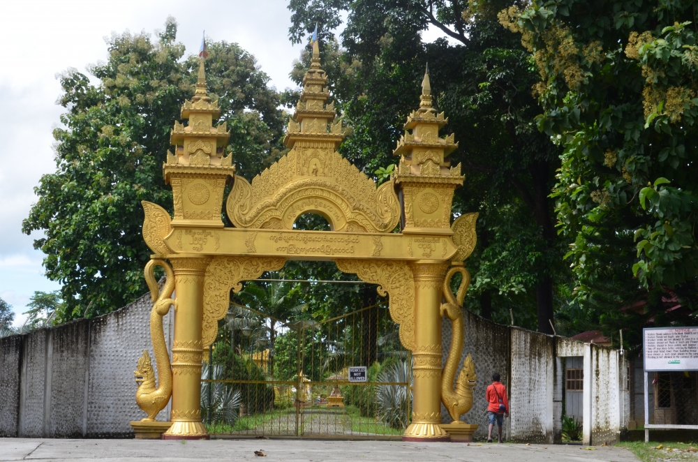 Fig. 1: Entrance gate of the Kongmu Kham (golden pagoda monastery), Tengapani, Arunachal Pradesh. Theravada monasteries of Arunachal Pradesh are distinguishable from the surrounding village dwellings and other structures by their attractive architecture. The entrance gates of these monasteries are decorated with Buddhist symbols and floral ornamental patterns and their boundaries are marked with bamboo fencing or concrete walls (Courtesy: Ajanta Das)