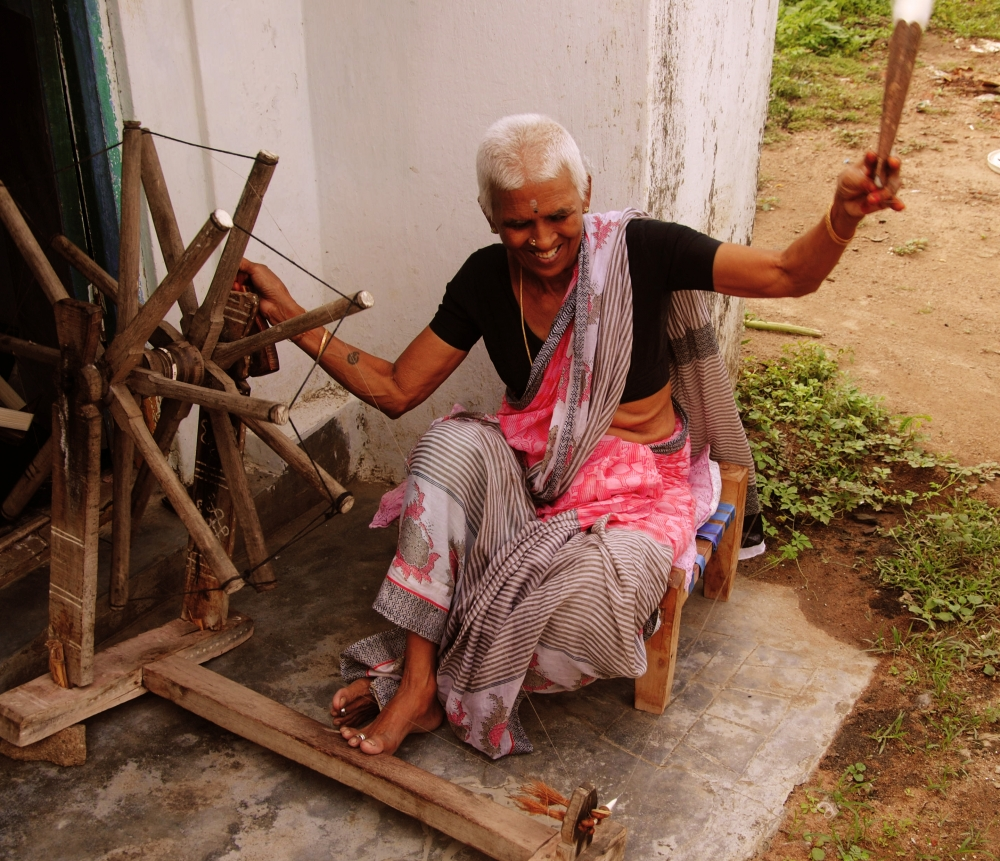 A spinner on her traditional charkha. She turns the wheels of the charkha with her right hand, while she draws and twists the cotton to make yarn with her left hand before winding it around the spindle (Courtesy: Samyuktha Gorrepati)