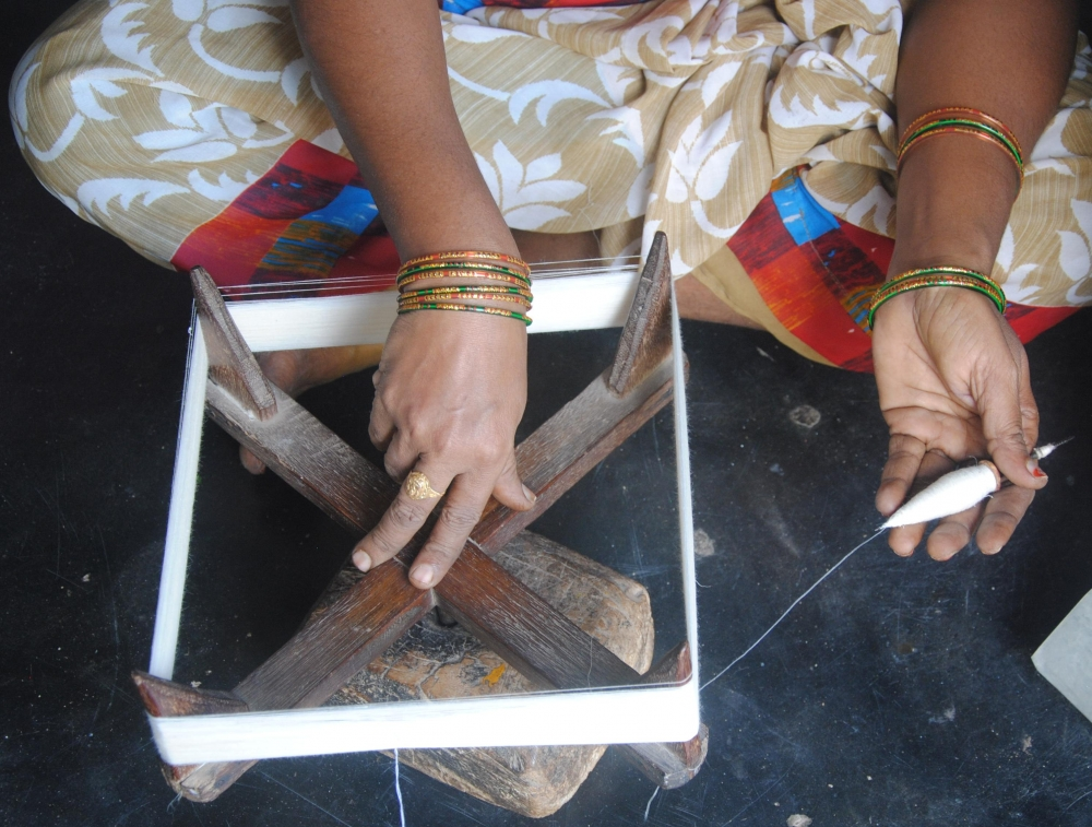 A spinner engaged in making a hank out of handspun yarn. She rotates the frame with her right hand while holding the spindle with her left hand as the yarn from the spindle reels off and winds around the frame. The hank is then taken off the frame, twisted and handed over to the weaver. A handspun hank is 1,000 metre in length (Courtesy: Samyuktha Gorrepati)