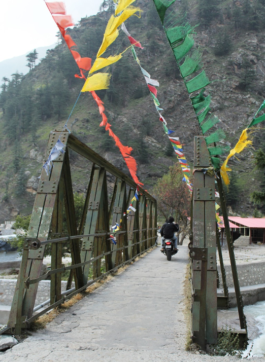 Fig. 1: One of the bridges leading to Bagori. The village is accessible only on foot or on a two-wheeler. The Tibetan prayer flags fluttering on the bridges showcase the probable Buddhist influence (Photo: Sweta Kandari)