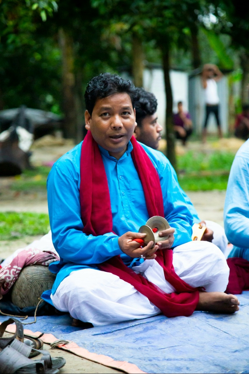 Fig. 7: Saral Sarkar playing his kartal (a percussion instrument) inside the dohar, the innermost circle of the performance space reserved for musicians.