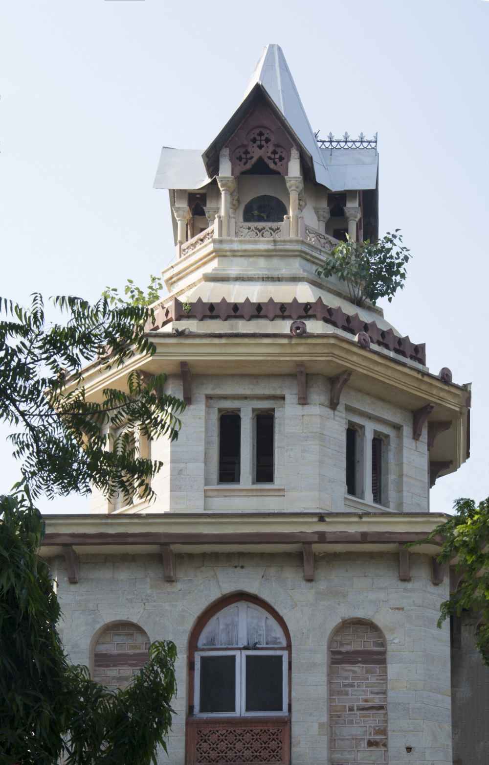 Fig.3: The top floor of the Mayo Hospital ghanta ghar shows the black iron, circular clock face, partially covered by the balcony railing. The clock is not in a functioning condition anymore