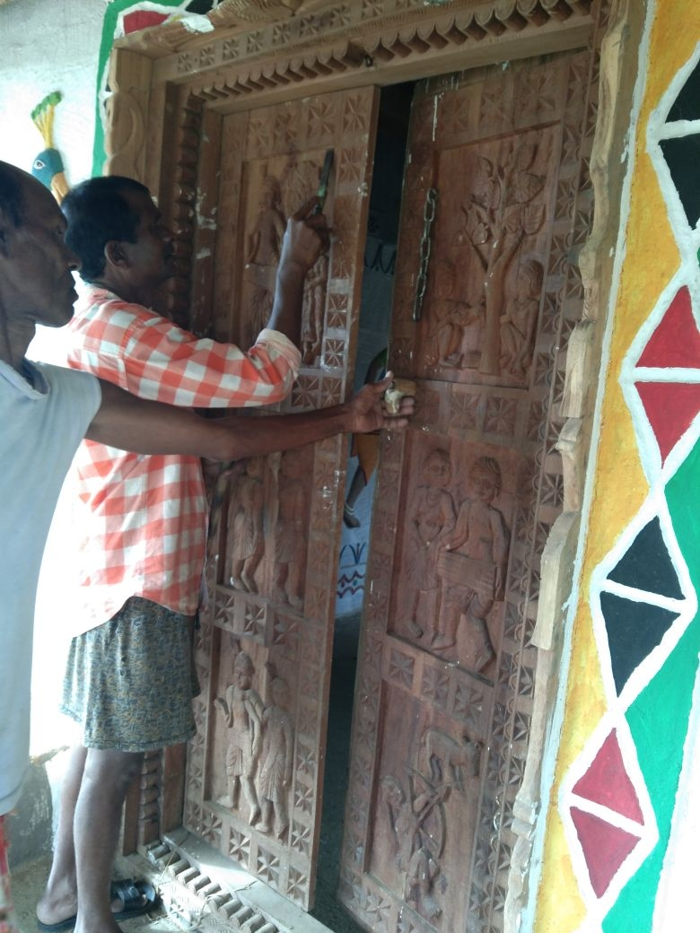 Artists carving out designs on the house door