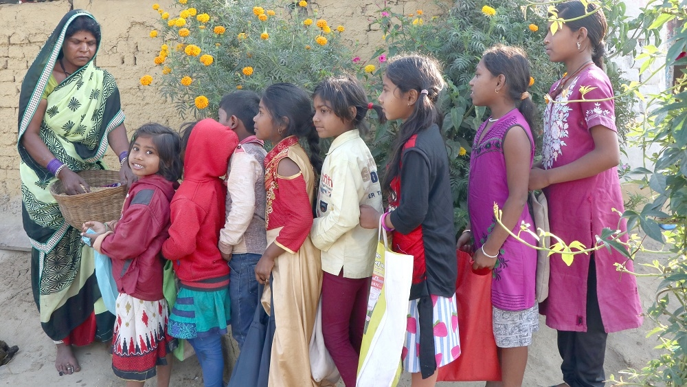Children lined up in front of a house to receive grains
