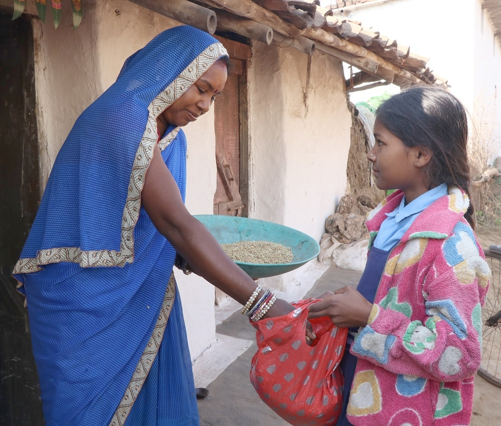 A girl receiving grain from a house lady during Chheri Chhera