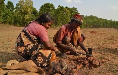 चित्र  1. पोलपोल पाट गाँव के बिरेश्वर असुर लौह पत्थरों के टुकड़े करते हुए। साथ में सखुआपानी गाँव की सुषमा असुर। (फोटो: विजय गुप्ता, सखुआपानी, नेतरहाट, 14 मई 2013)