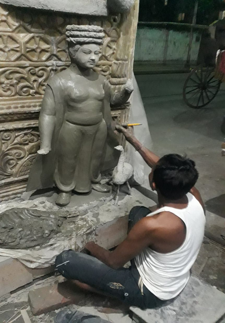 A kumar applies a coat of clay on an idol. (Courtesy: Aaheli Sen)