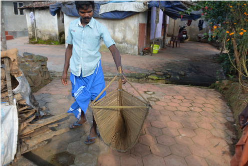 Fig. 4. A Paniya youth with an indigenous fishing trap (Courtesy: Vasundhara Krishnan)