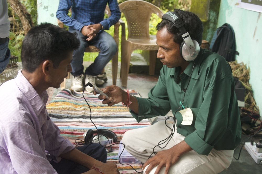 Fig. 2: Former team member of Mandakini ki Awaaz, Ramesh Rangeela, records a community member's message in Jaikhandi. In Mandakini river valley, most villages are not easily accessible; team members from Mandakini ki Awaaz usually organise field visits to villages in their catchment community to speak to community members about relevant issues and record artistes and musicians. These field visits provide musicians who may not be able to physically travel to the community radio station an opportunity to have their music recorded and showcased on the radio (Photograph by Shweta Radhakrishnan/ Courtesy: People's Power Collective)