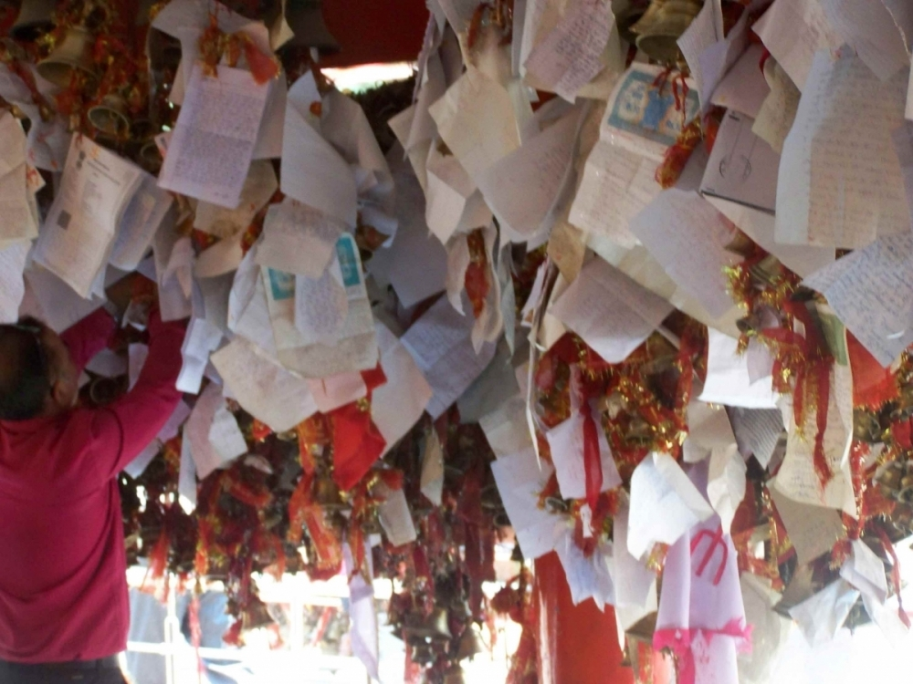 Many tourists are drawn to this unusual sight of hanging prayers. They hang in between hundreds of bells that are offerings to the deity for favours/ justice received.