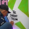 Pranay (Sketchy Artist), a graffiti artist from Dharavi, finishing a graffiti with the signature of his institute, the Dharavi Dream Project (Courtesy: Goutham Raj Konda)